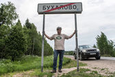 Taking picture by the road sign of village Buhalovo, meaning in russian heavy drinking — ストック写真