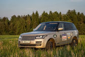 Suv car in high grass of russian field — Stock Photo