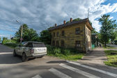Luxury suv car by a Log house of the nineteenth century in Russia, Yaroslavl — Stock Photo