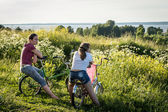 Two teenage Girls with bicycles on a meadow, Russia — Stock Photo