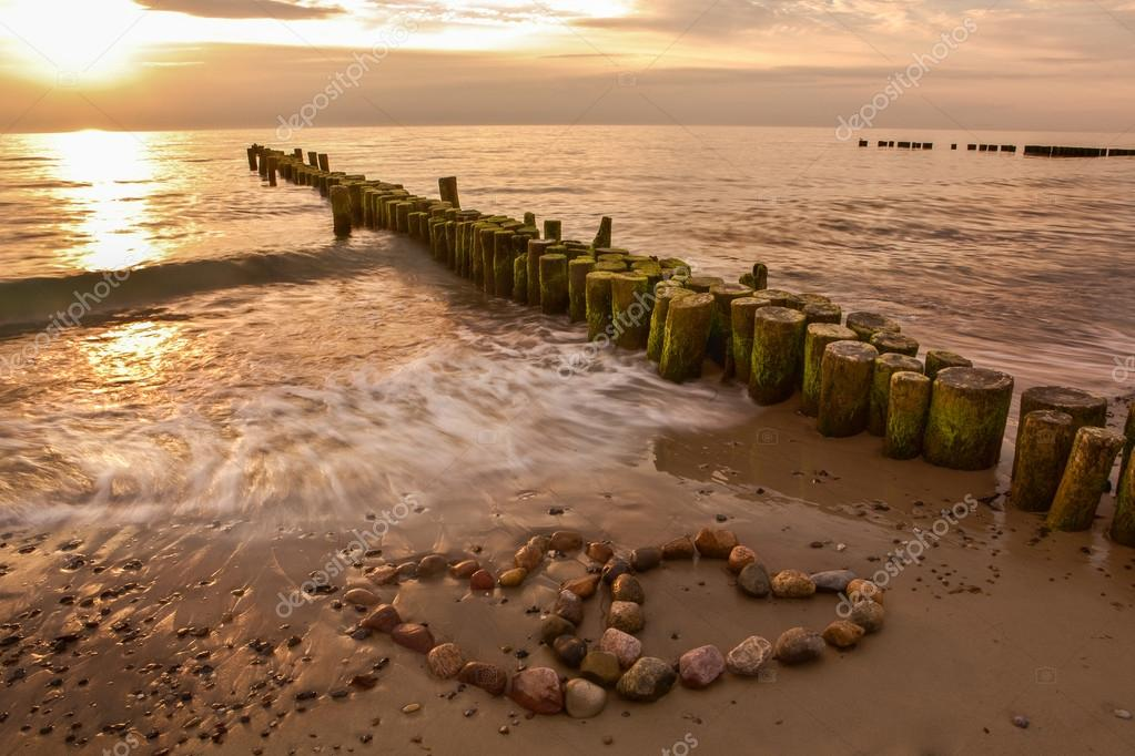 Romance at the beach with two sentimental hearts side by side formed of stones on a tranquil seashore lit by beautiful soft warm evening light at sunset — Stock Photo #18240009