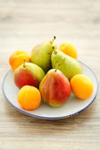 Plate of delicious fresh pears and apricots — Stock Photo