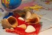 Seashells and small globe on a book with a geographical map. — Stock Photo