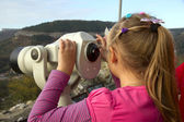 Girl looks into the distance through a telescope — Stock Photo