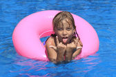 Girl swimming in the pool with pink rubber ring and shows tongue. — Stock Photo