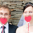 Happy young wedding couple with decorative cardboard hearts in h — Stock Photo
