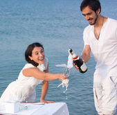 Young couple with champagne by the sea — Stock Photo