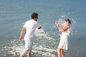 Young couple fighting pillows on the beach — Stock Photo