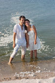Young couple standing in the sea and laughing after the fight pillows — Stock Photo