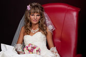 Blonde bride sitting in a red chair in the studio on a black background — Stock Photo