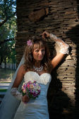 Beautiful bride with bouquet near stone wall — Stock Photo