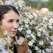 Stock Photo: Beautiful young brunette woman in white flowers outdoors
