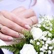 Hands with wedding rings and wedding bouquet — Stock Photo