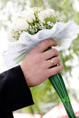 Wedding bouquet at groom's hands — Stock Photo