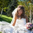 Beautiful bride sitting on the grass — Stockfoto