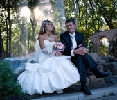 The newlyweds sitting on the rock in the park — Stock Photo