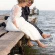 Portrait of romantic couples sitting over wooden pier — Stock Photo