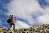 Hiker with stick on a background of sky — Stock Photo