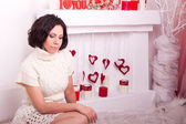 Young woman sits on fur coverlet near fireplace — Stock Photo