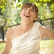 Beautiful bride laughs about wood — Stock Photo #45582127