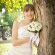 Beautiful bride laughs about wood — Stock Photo #45582137