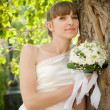 Beautiful bride laughs about wood — Stock Photo #45582139