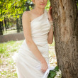 Beautiful bride laughs about wood — Stock Photo #45582145