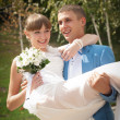 Groom carries his bride in the arms — Stock Photo #45582147