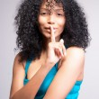 Mulatto girl signalling to be quiet — Stock Photo #23216236
