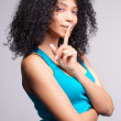 Mulatto girl signalling to be quiet — Stock Photo
