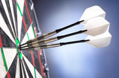 Three darts in bullseye of dartboard — Foto de Stock