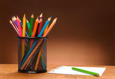 Blank sheet of paper and colored pencils on a wooden table — Stock Photo