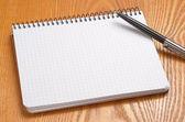 白木桌上用黑色钢笔笔记本 — 图库照片
