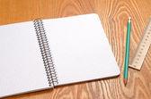 En vit obs bok med massor av utrymme för din text eller bild och en vanlig penna på ett trä skrivbord — Stockfoto