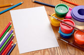 Blank sheet of paper with colorful pencils and paints — Stock Photo