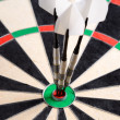 Three darts in bullseye of dartboard — Stock Photo