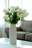Flowers in a vase on wooden table — ストック写真