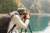 The proffesionalnyj photographer does shooting of mountain lake — Stock Photo