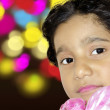 Happy girl child face with colorful bokeh abstract background — Stock Photo