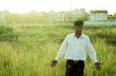 Farmer or businessman touching grass — Stock Photo