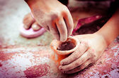 Hands playing with colors &  earthen pots — Stock Photo