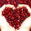 Pomegranate seeds shaping heart in hands — Photo #21871549