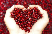 Pomegranate seeds shaping heart in hands — Photo