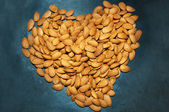 Heart shape from almond nuts texture — Stock Photo