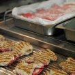 Stock Photo: Some meat cooking on grill in commercial kitchen