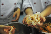 Some fresh shrimps handled by two chefs in a commercial kitchen — Stock Photo
