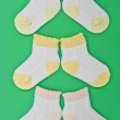 Three pairs baby socks on green background - Stock Photo