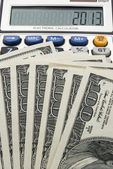 Us paper currency and calculator shows 2013 — Stock Photo