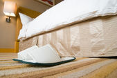 Slippers and bed in a hotel room — Stock Photo