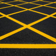 Cross yellow lines on blacktop — Stock Photo #19108555